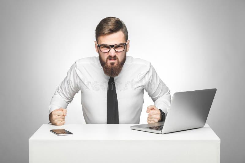 积极的恼怒的年轻上司画象白色衬衫的和半正式礼服在办公室坐,并且有心情,猛击桌和 库存图片