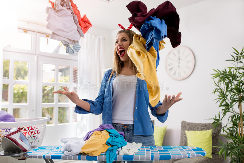积极的沮丧的妇女在天空中投掷洗衣店 免版税库存图片
