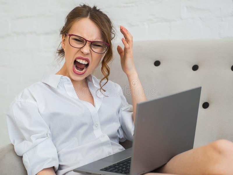 积极的职业妇女在家工作 有膝上型计算机的叫喊和沮丧的妇女 图库摄影