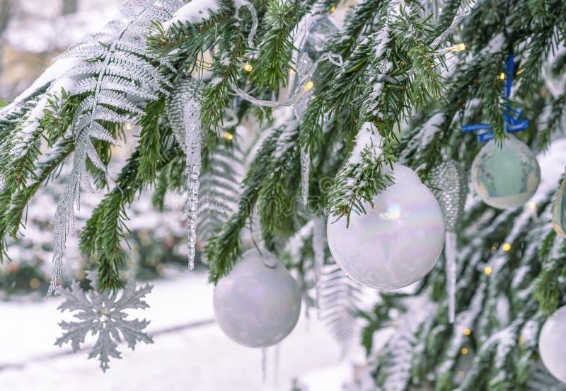 积雪的圣诞树用白色球、冰柱和诗歌选装饰 图库摄影