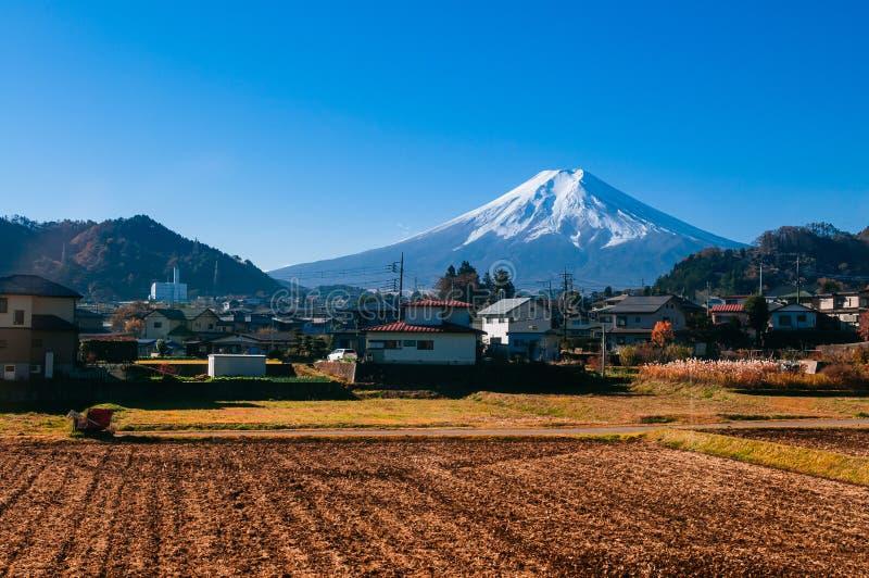 积雪的富士山和地方镇沿火车路线在Shimoyoshida -富士吉田市,日本 免版税库存图片