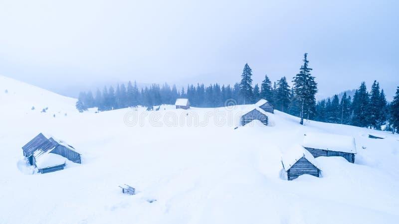 积雪的小屋顶视图在山的 免版税库存照片