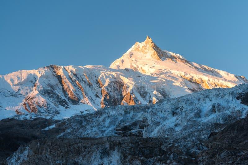 积雪的山美丽的景色在五颜六色的日出的在N 库存照片