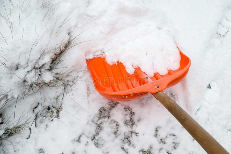 积雪的清除 在雪的橙色铁锹 库存照片