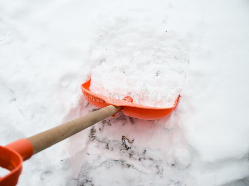 积雪的清除 在雪的橙色铁锹 免版税库存照片