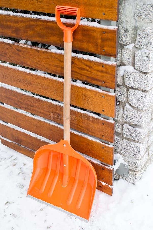 积雪的清除 在雪的橙色铁锹 库存图片