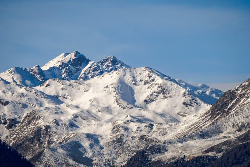 积雪覆盖的山美丽的射击在与清楚的天空的一好日子在背景中 免版税库存照片