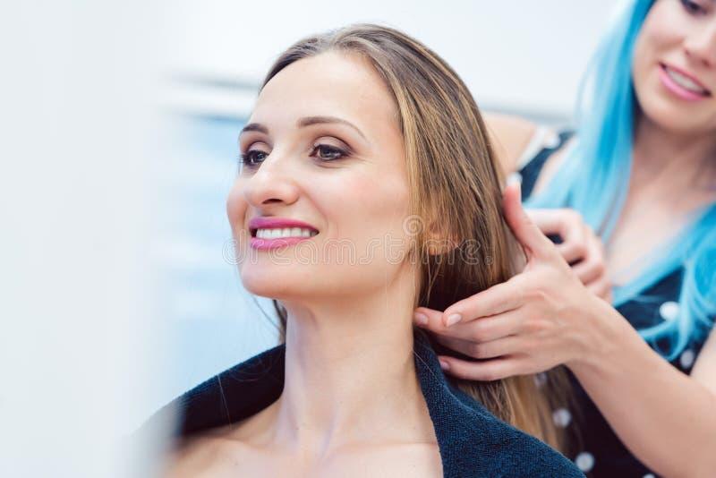 称呼妇女客户的头发的熟悉内情的美发师 库存照片