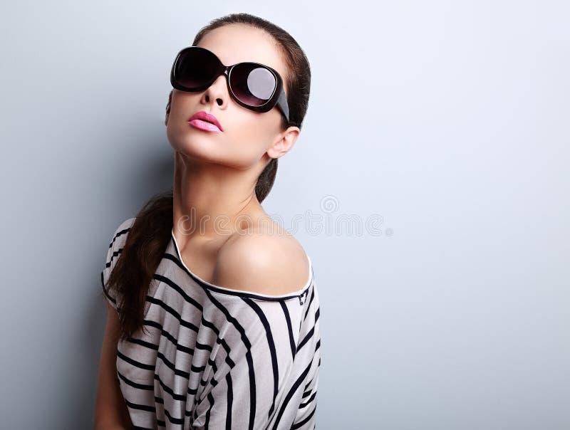 称呼摆在时尚太阳镜和现代blou的女性模型 免版税库存照片