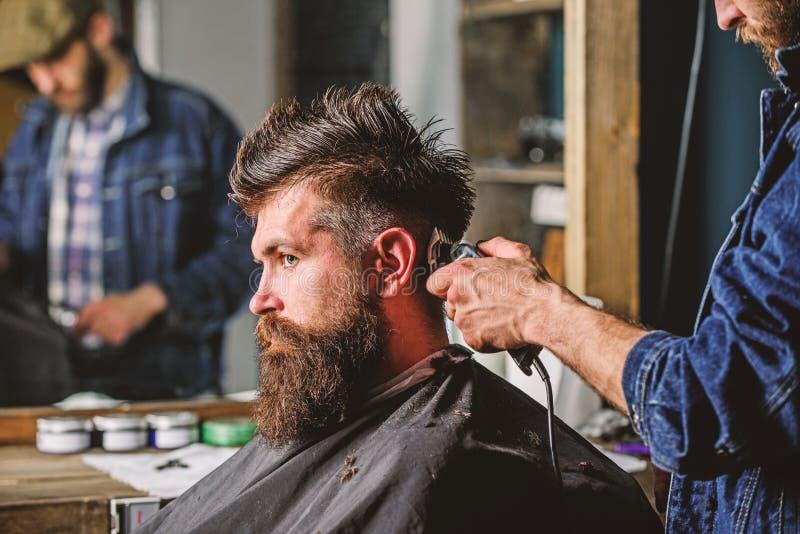 称呼残酷有胡子的客户的头发的有飞剪机的理发师 有头发剪刀工作的理发师在有胡子的人的发型 免版税库存图片