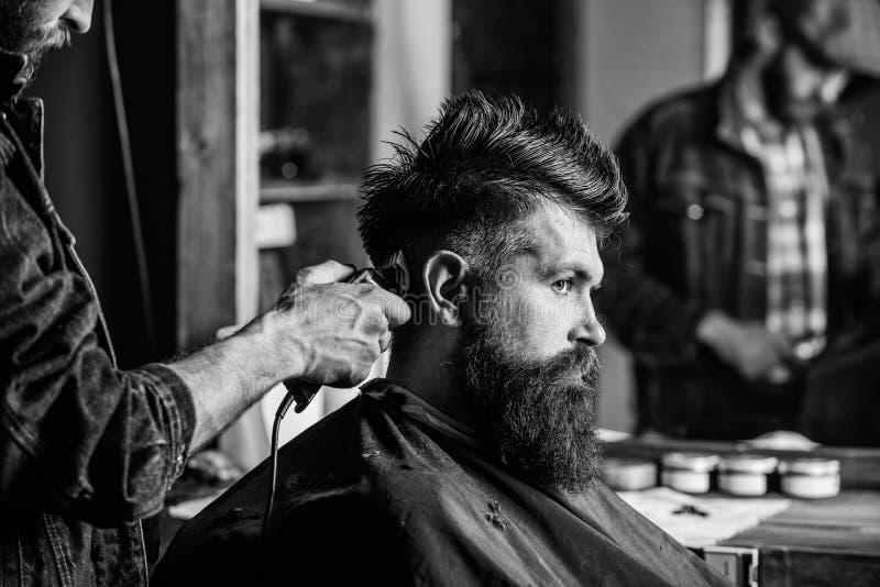 称呼残酷有胡子的客户的头发的有飞剪机的理发师 有头发剪刀工作的理发师在有胡子的人的发型 库存照片