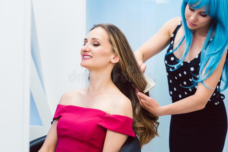 称呼顾客的头发的妇女美发师在她的商店 库存照片