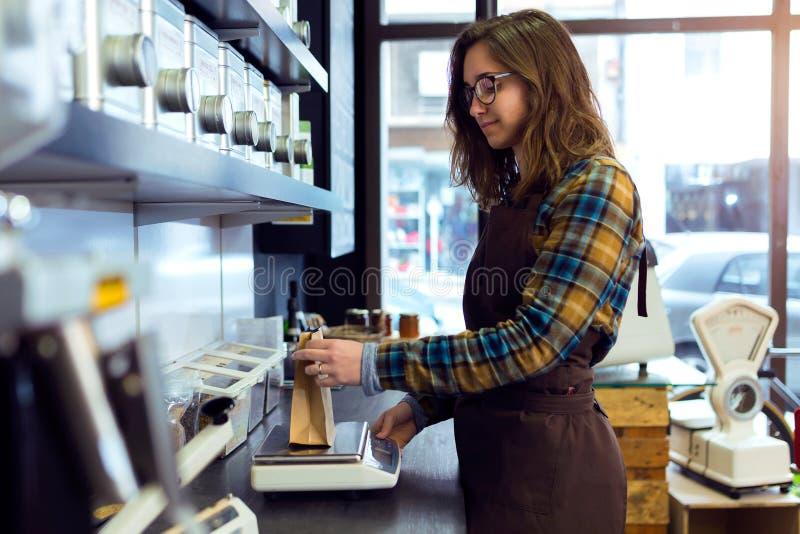 称在一家零售店的美丽的年轻女推销员咖啡豆卖咖啡 免版税库存照片