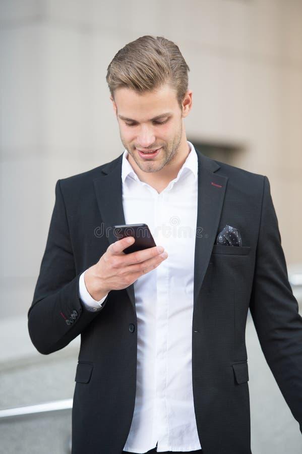 称的商人客户举行智能手机都市背景defocused 人经理通话 人与 免版税库存图片