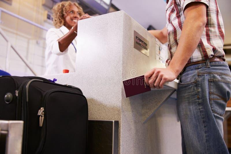 称行李的乘客在机场登记 免版税库存图片