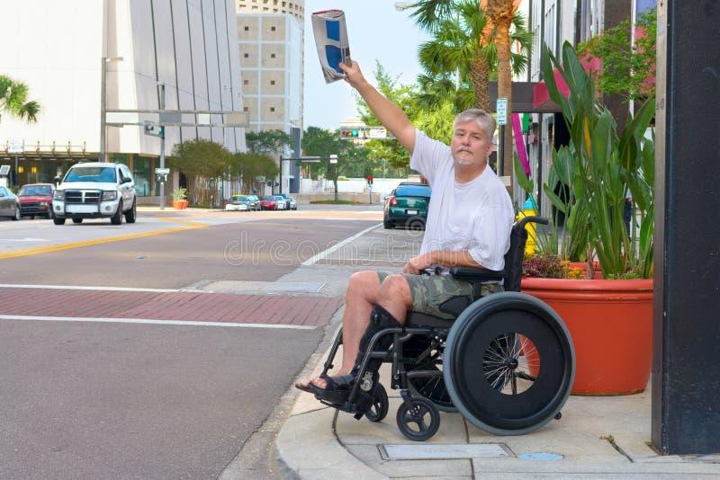 称赞出租汽车挥动的报纸的轮椅的有残障的人 免版税库存照片