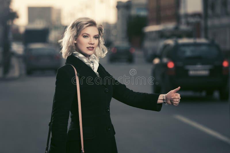 称赞在城市街道的年轻时尚妇女一辆出租车 免版税库存图片