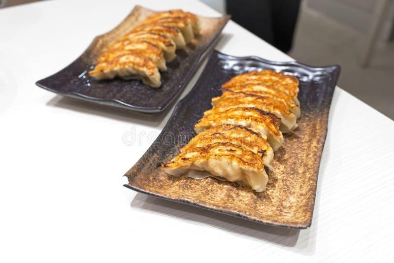 称Gyoza或娇子队的日本饺子在中国, Gyoza用猪肉和菜, Gyoza的关闭在黑色的盘子 免版税图库摄影