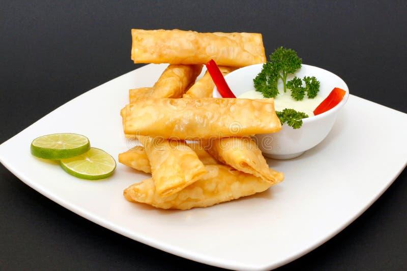称Tequenos的拉丁美洲的开胃菜由油煎的馄饨制成充满乳酪和供食与鳄梨调味酱捣碎的鳄梨酱 免版税库存照片