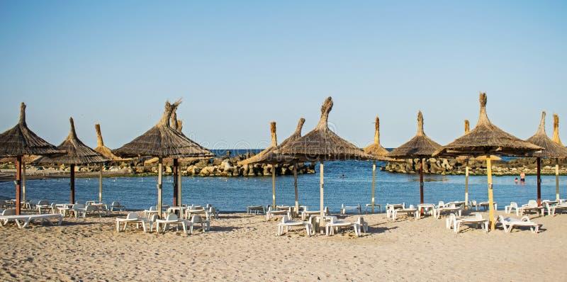 秸杆伞和sunbeds在沿海岸区 没人海滩的 海上的第一个夏日 免版税图库摄影