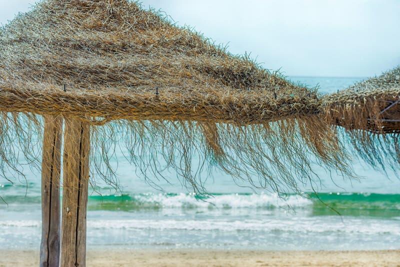秸杆在沙子海滩绿松石海的沙滩伞挥动蓝天背景 明亮的阳光 暑假旅行癖旅行 免版税图库摄影