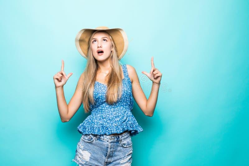 秸杆夏天帽子的指向食指在拷贝空间的微笑的年轻女人画象隔绝在黄色背景 人们 免版税库存照片