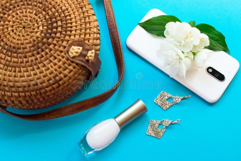 秸杆时髦的现代妇女的夏天袋子和电话、耳环和茉莉花花在蓝色背景 E 免版税图库摄影