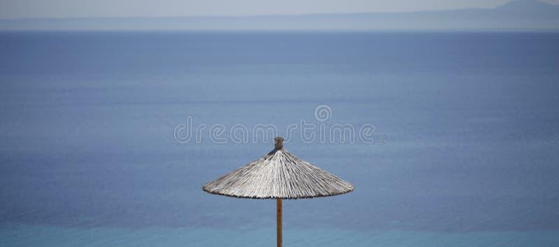 秸杆有蓝色海的沙滩伞背景的 库存照片