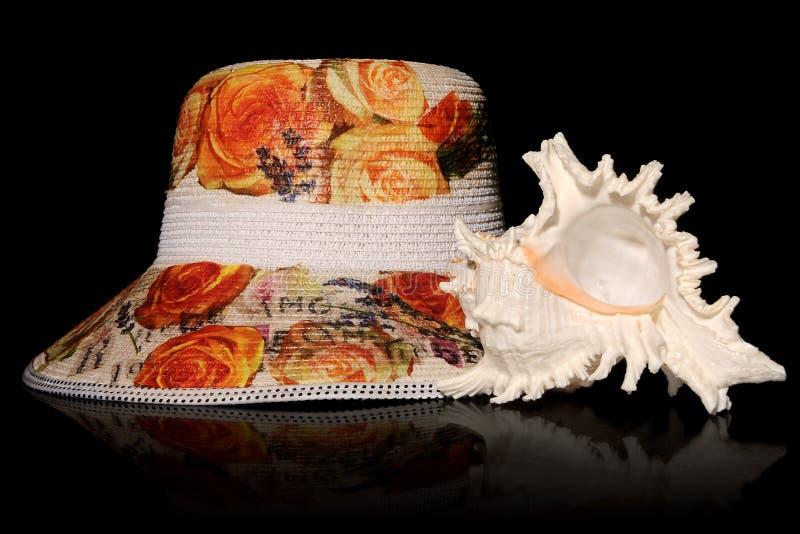 秸杆用花装饰的帽子和骨螺等海壳 免版税库存图片