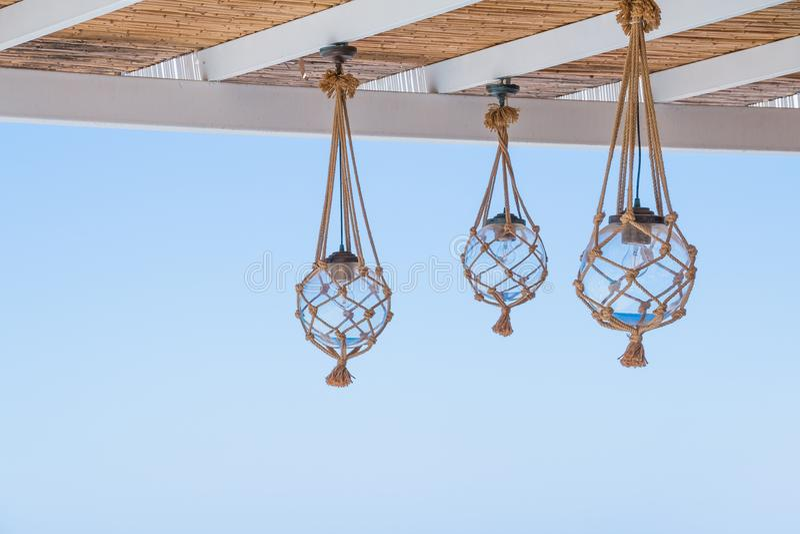秸杆盖子海边大阳台或游廊的屋顶与垂悬的灯笼和看法对蓝天 许多电灯泡 库存图片