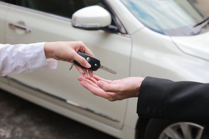 移交一辆新的汽车的汽车推销员钥匙给年轻商人 库存照片