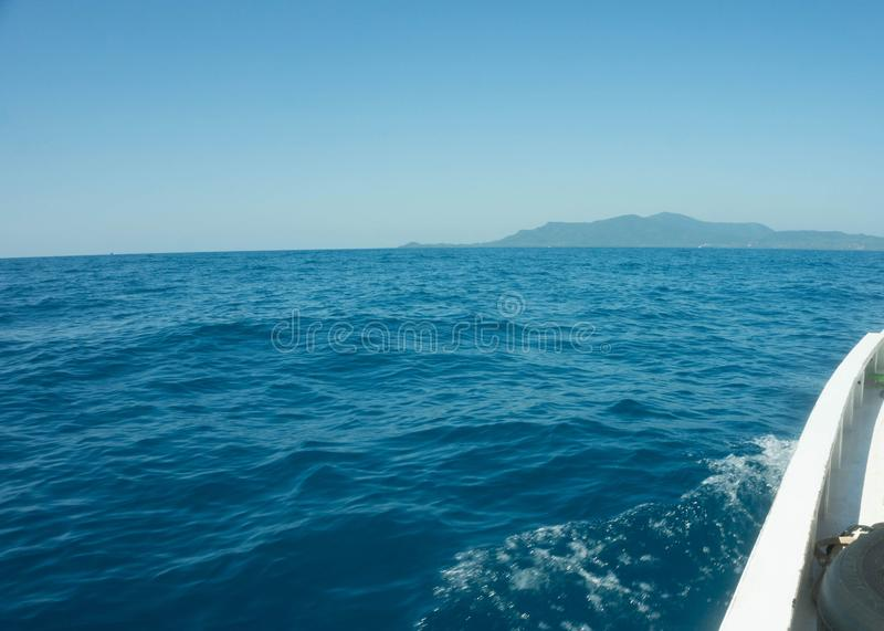 移动与速度的小船有水飞溅视图从有海岛的前面甲板距离的 免版税库存照片