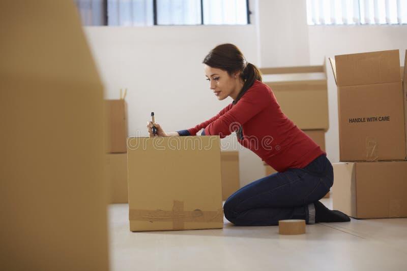 移动向与配件箱的新的公寓的白种人妇女 免版税库存照片