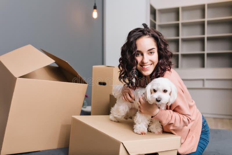 移动向年轻俏丽的妇女的新的公寓有小犬座的 变冷在床周围有宠物的纸盒箱子,微笑 图库摄影