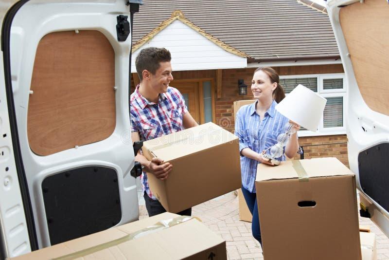 移动向新的家庭卸载的撤除范的年轻夫妇 库存图片