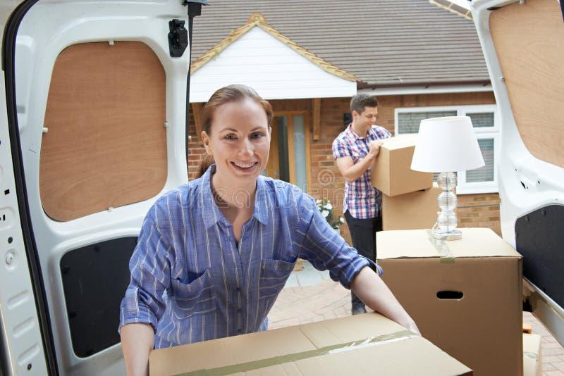 移动向新的家庭卸载的撤除范的年轻夫妇 免版税库存照片