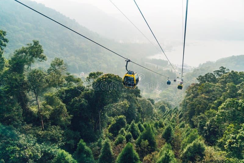 移动在与绿色树的山的长平底船推力在日月潭索道区域在渔池乡,南投县,台湾 免版税库存照片