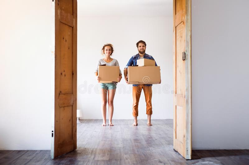 移动在新房里的年轻夫妇,拿着箱子 库存图片