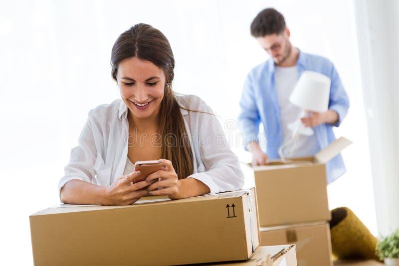 移动在新的家的美好的年轻夫妇 免版税库存照片