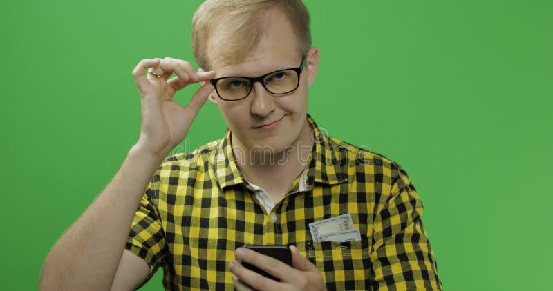 移动或发短信在智能手机的玻璃的白种人人在他的手上 库存照片