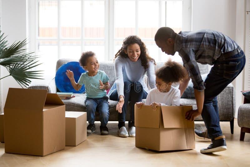 移动新的公寓的愉快的嬉戏的非裔美国人的家庭 免版税库存图片