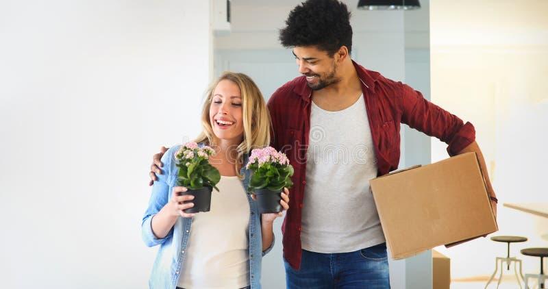 移动新的家和打开carboard箱子的年轻夫妇 库存照片
