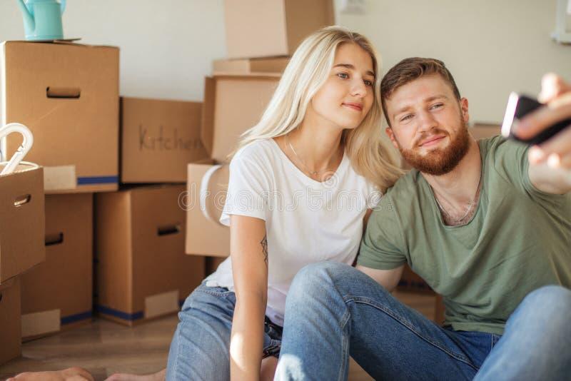 移动新的家的夫妇 坐地板和放松在打开以后 做与智能手机的selfie 库存照片