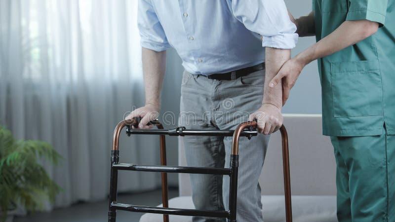 移动有走的框架和护士支持的老人院的资深患者 免版税图库摄影