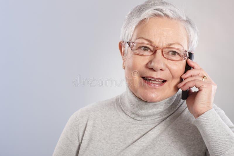 移动电话微笑的老妇人 免版税库存图片
