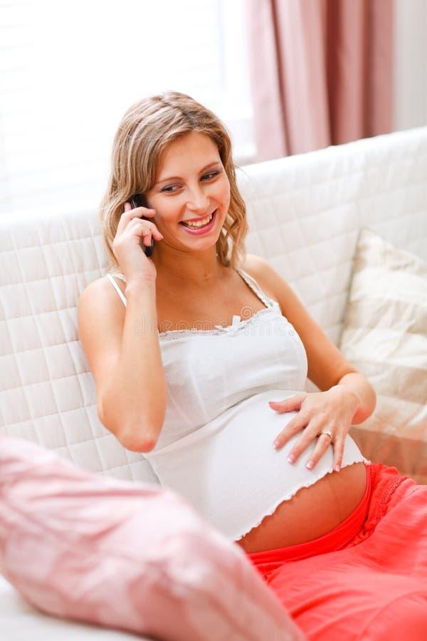 移动电话怀孕的告诉的妇女年轻人 库存照片