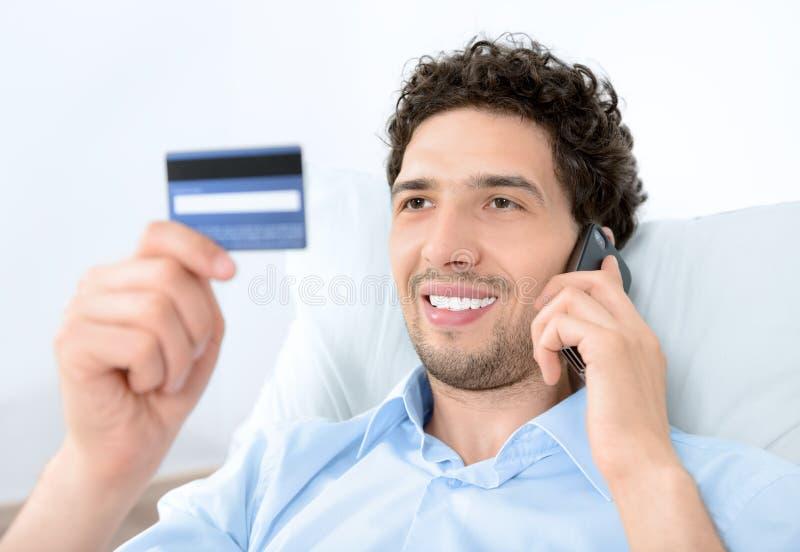 移动电话的年轻人与信用卡 免版税库存照片