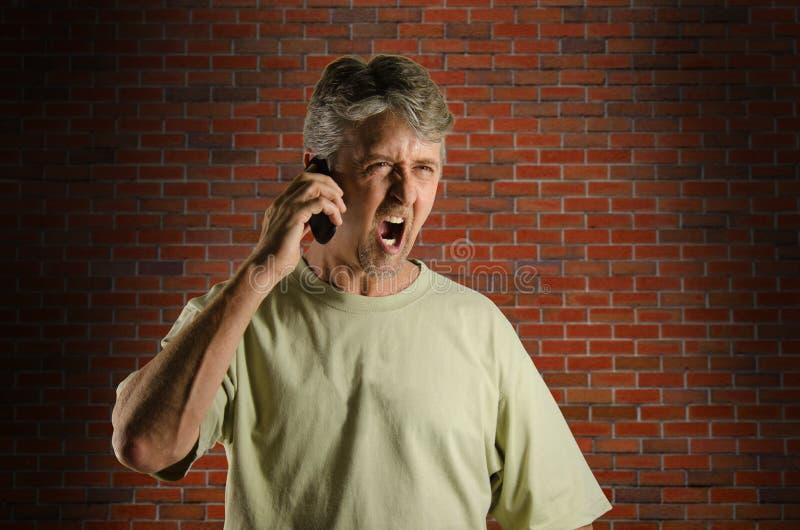 移动电话的恼怒的叫喊的人 免版税库存照片
