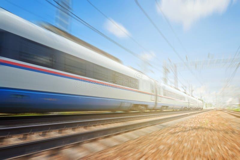 移动超高速火车的侧视图在与铁路基础设施的路轨途中跑在与火光e的被弄脏的背景中 库存照片