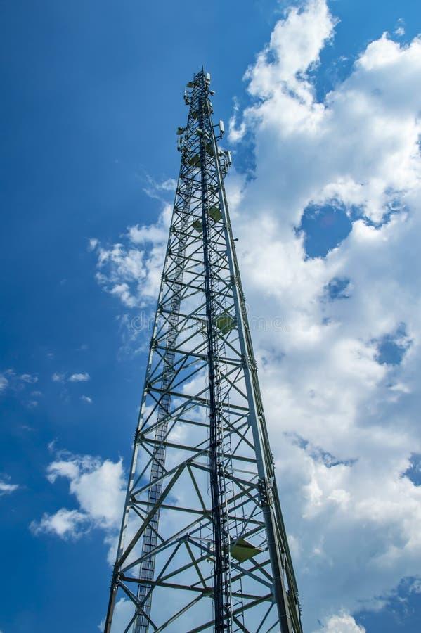 移动通信塔反对天空蔚蓝的与白色云彩 免版税库存照片